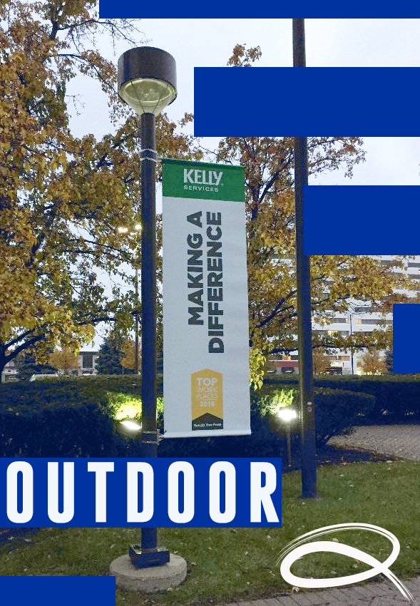 a banner for kelly services making a difference award hung from a lamppost outside and it says outdoors on the bottom corner