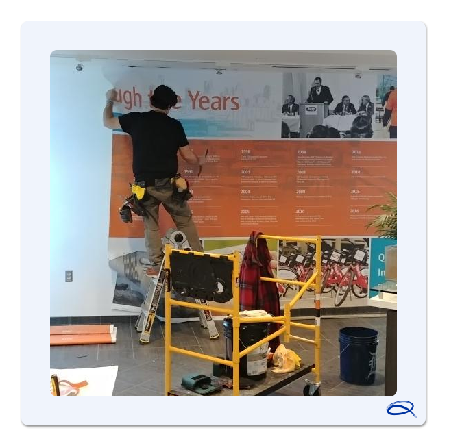 a member of the quantum graphics installation team installs a new wall graphic at the headquarters of hap using a squeegee and ladder